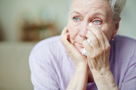 Upset senior woman wiping tears with handkerchief