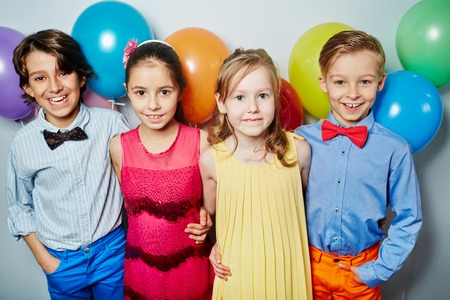 child birthday: Row of friendly kids embracing at birthday party
