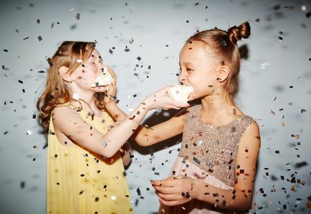 confetti: Two girls having fun with birthday cake under confetti rain
