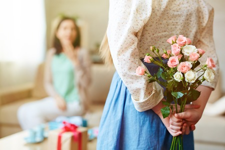 gift behind back: Girl holding bunch of roses behind back