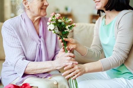 Junge Frau, die ihre Mutter frische Rosen gibt