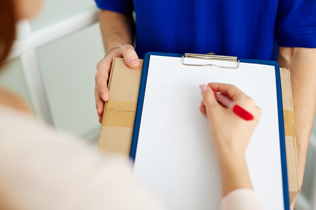 hand paper: Woman signing for parcel in cardboard box