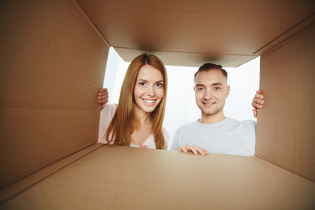Young couple looking into open cardboard box