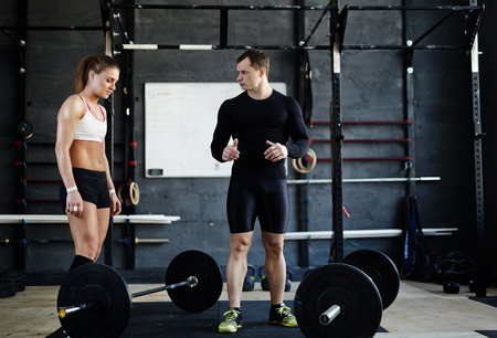 activewear: Fit woman in active-wear and her trainer in gym Stock Photo