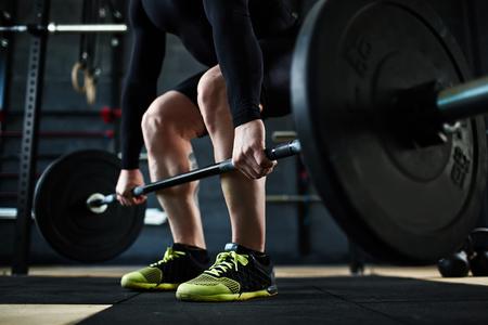 фитнес: Активный молодой человек с тренировки в тренажерном зале со штангой