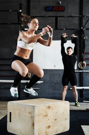 man gym: Fit woman in active-wear training on jump-boxes