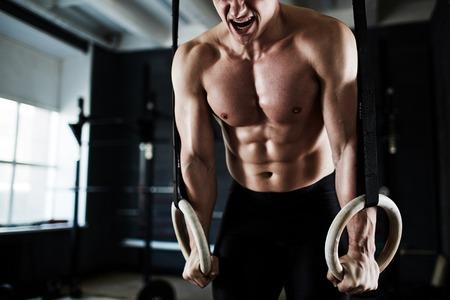 fitness hombres: Hombre joven activo haciendo el esfuerzo durante el entrenamiento en las instalaciones deportivas