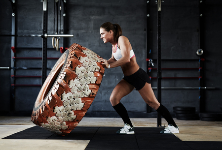 Active and strong woman flipping tyre in gym