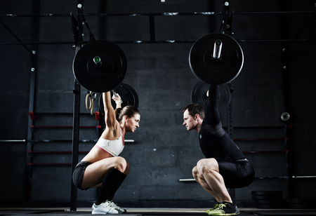 Active young man and woman lifting heavy barbells opposite one another