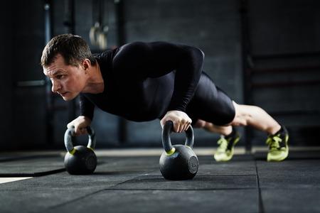 활성 젊은 남자 체육관에서 팔 굽혀 펴기를하고 스톡 콘텐츠