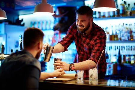 barra de bar: camarero feliz que hace la bebida para el cliente Foto de archivo