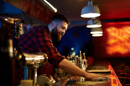 adult entertainment: Bearded barman wiping bar counter Stock Photo