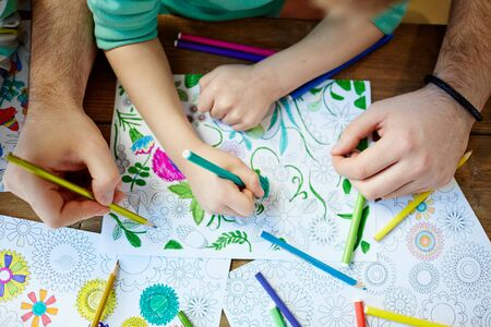 creative pictures: Child and parent coloring creative pictures with crayons Stock Photo