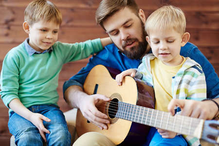 Young man showing his sons how to play guitar