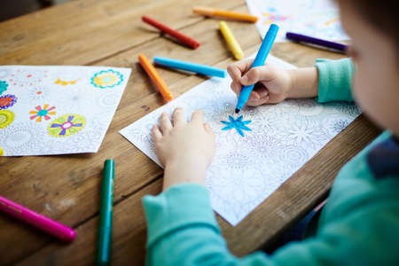 creative pictures: Little boy coloring creative pictures with highlighters