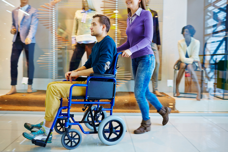 wheeling: Woman wheeling a disabled young man in shopping mall Stock Photo