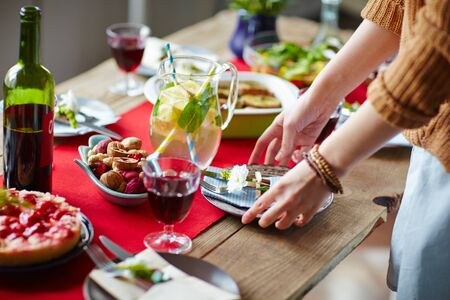 table setting: Woman putting plates on table for dinner