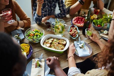 eating dinner: Friends having dinner at a wooden table