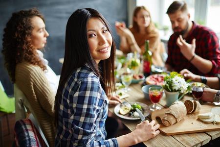 grupo de hombres: Mujer bonita que se sienta a la mesa con amigos y tener la cena