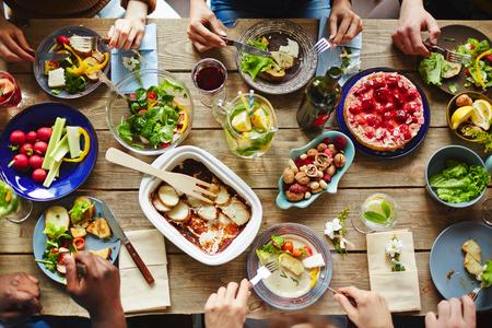 Persone che hanno una ricca cena con verdure fresche e farina fatta in casa