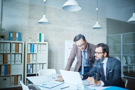 ビジネス ポイントに話している 2 人の男性同僚 写真素材