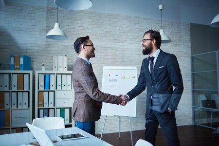 business deal: Partners shaking hands in office Stock Photo