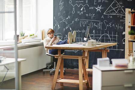 break in: Young designer or architect with smartphone having break in office