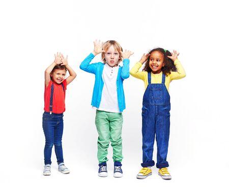 Lustige Kinder in Casual-Wear, die Gesichter bildet