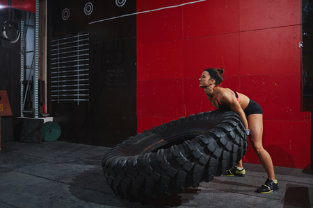 strong woman: Strong woman flipping tyre during training in gym