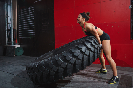Strong woman flipping tyre during workout