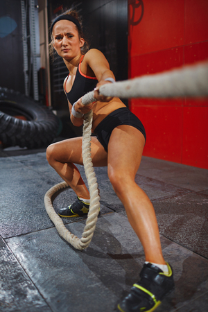 woman rope: Strong young woman in active-wear pulling rope Stock Photo