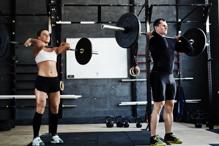 physical training: Active young man and woman lifting heavy barbells