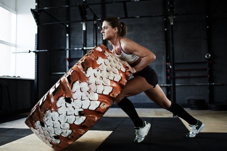 activewear: Strong woman in active-wear flipping tyre Stock Photo
