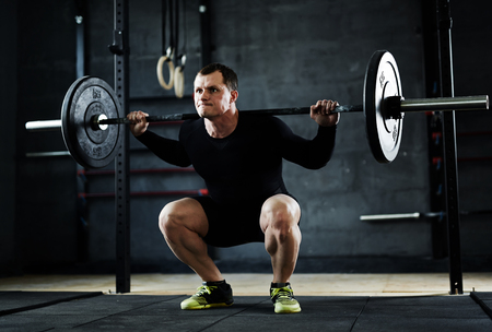 Active man lifting weight during workout in gym Stock Photo