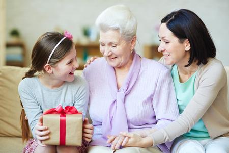 dia: Las mujeres jóvenes y de edad avanzada que buscan en caja de regalo en manos de adolescente