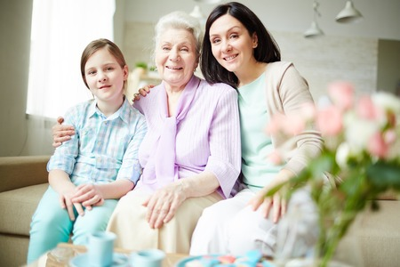 Cheerful young woman, elderly one and teenage girl looking at camera at home Stock fotó