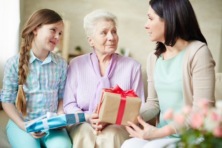 jovenes felices: Two women and teenage girl with presents talking at home Foto de archivo