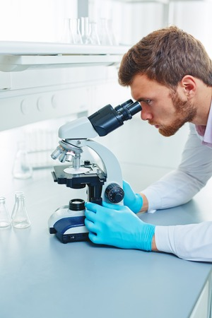 scrutinize: Serious chemist carrying out microbiological investigation in lab Stock Photo