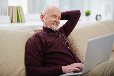 technology career: Mature man with earphones listening to music and networking with laptop