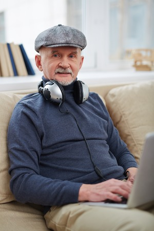 mature man: Mature man with headphones typing on laptop Stock Photo