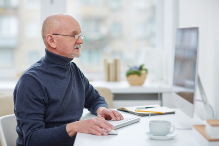 technology career: Mature man sitting in front of computer monitor Stock Photo