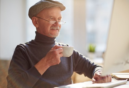 work addicted: Happy mature man in cap, eyeglasses and pullover drinking tea in front of computer