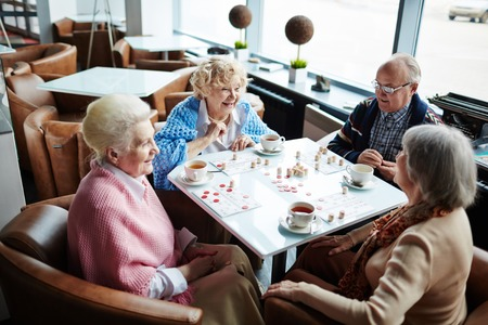 Grupo de personas mayores de amistad que juegan lotería en café Foto de archivo - 54993798