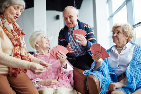 Group of friendly seniors playing cards at leisure Stock Photo