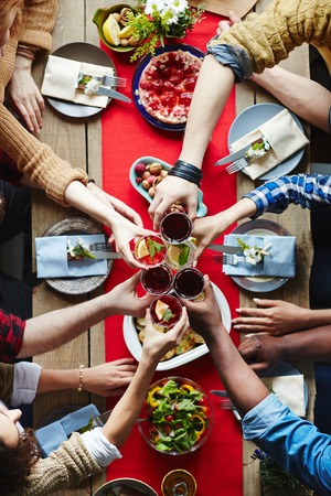 Group of friends toasting over dinner table