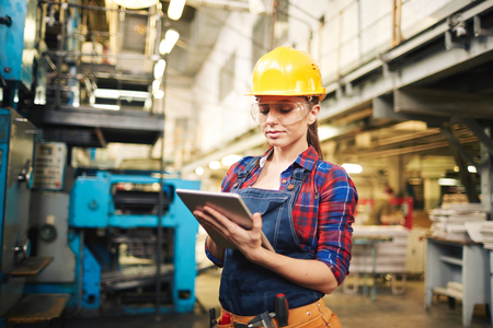 executive helmet: Young woman in helmet networking at modern plant Stock Photo