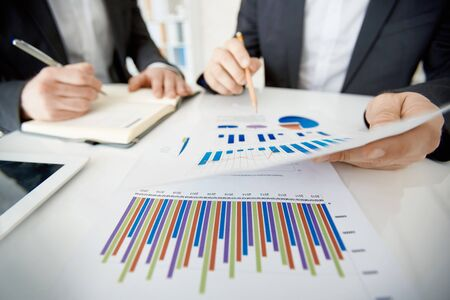 discussing: Two businessmen discussing document with chart Stock Photo