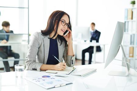 Secretaria ocupada que llama por el teléfono celular mientras que planea el trabajo