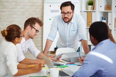 briefing: Young Asian businessman looking at colleagues at briefing Stock Photo