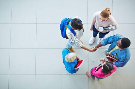 personas saludandose: Estudiantes cómodos apretón de manos con un grupo de niñas cerca